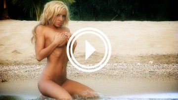 Jennifer Fox naked and covered in sand.